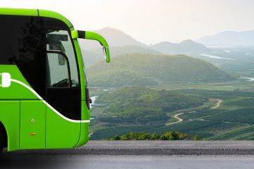 Electric,Tourist,Bus,In,Front,Of,Mountain,Valley