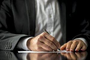 Conceptual,Image,Of,A,Man,Signing,A,Last,Will,And