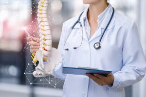 A,Medical,Worker,Shows,The,Spine,On,Blurred,Background.