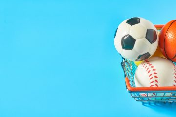 Different,Balls,In,Metal,Market,Basket,On,Blue,Background.,Purchasing